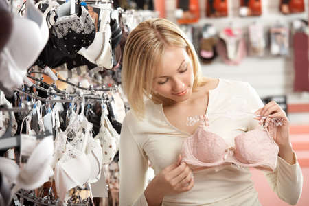 lace bra: The woman considers a brassiere in shop   Stock Photo