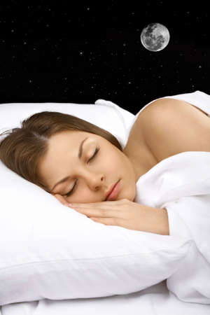The woman sleeps in white bed against the night sky and the moon   photo