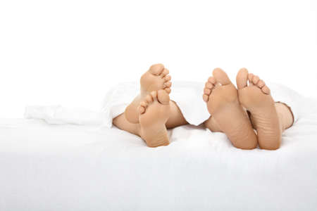 Heels of two people stick out from under a white bed-sheet, isolated photo