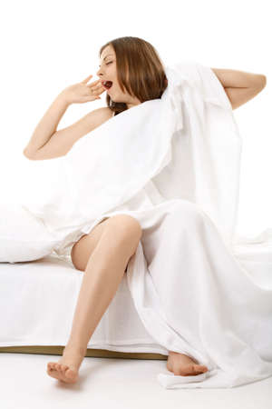 The young woman sits in bed and yawns, isolated   photo
