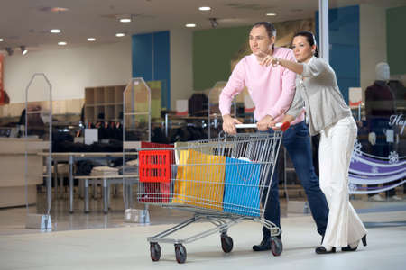 Young married couple in shop with the cart against show-windows