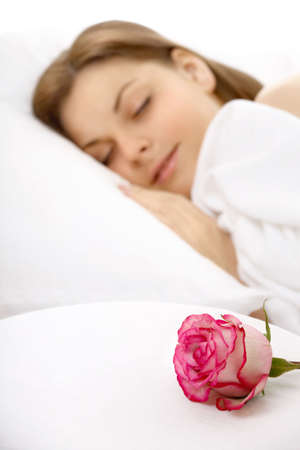The girl sleeps in bed, nearby there is a rose, isolated   photo