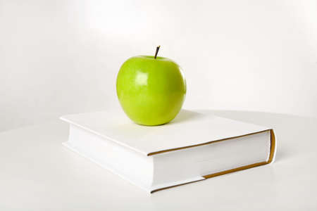 school table: Green apple on the thick book, isolated Stock Photo
