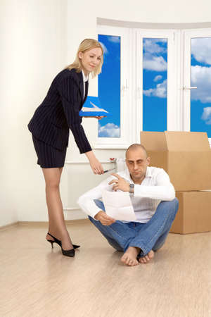 The woman allows to the man to sign papers in new apartment photo