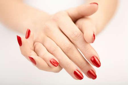 Sheaf de deux soigné des mains avec le rouge de manucure, isolé