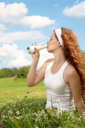 Profile of the beautiful girl drinking milk against a meadow and the blue sky