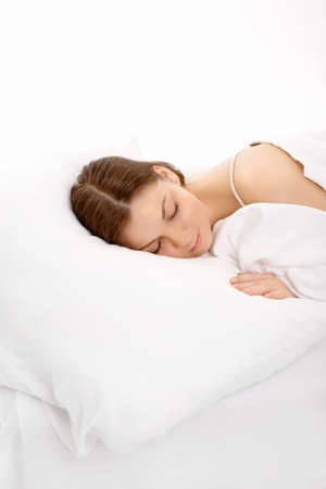 The young girl sleeps in the white bed, isolated photo
