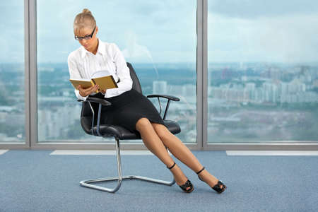 The beautiful business woman on an armchair at office reads the book photo