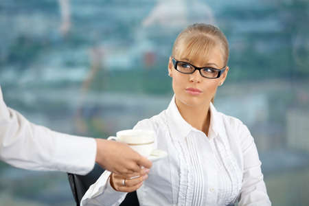 The business woman at office takes a cup which to it have brought photo