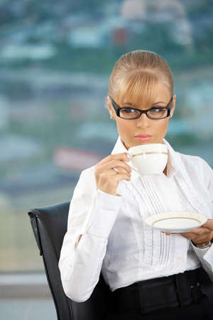 Beautiful businesswoman drinks morning coffee at office photo