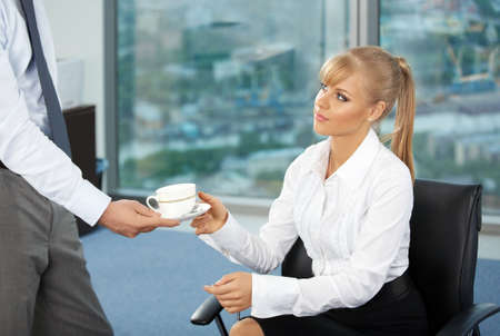 The beautiful business woman at office accepts a cup of coffee from the colleague photo