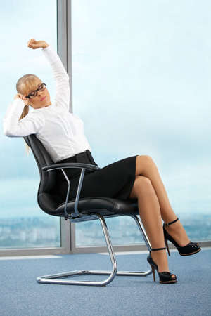 The stretching blonde at office against a window photo