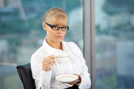 The beautiful business woman with a coffee cup in a hand at office photo