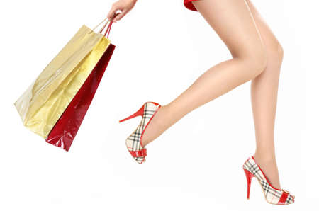 Beautiful legs of the running woman holding in a hand packages with purchases Stock Photo