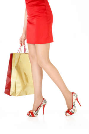 Legs of the woman holding in a hand a bag with purchases, isolated photo
