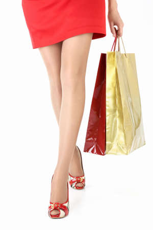 Legs of the going woman with the packages, isolated on a white background photo