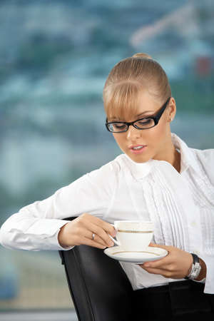 The attractive business lady with a coffee cup at office photo