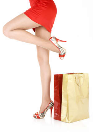 Side view of beautiful female legs near to the gift packages, isolated photo