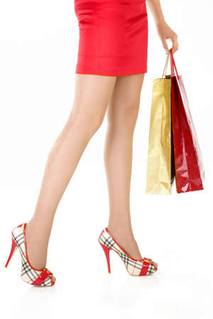Side view of female legs, hands hold the gift packages, isolated photo
