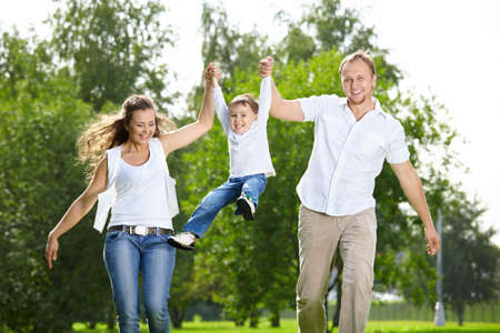 Parents with the small son frolic on the nature Stock Photo - 5543367