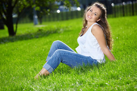 Smiling woman sits on a summer lawn Stock Photo - 5543369