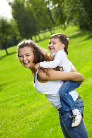 Cheerful mum and son frolic in a summer garden Stock Photo - 5556687