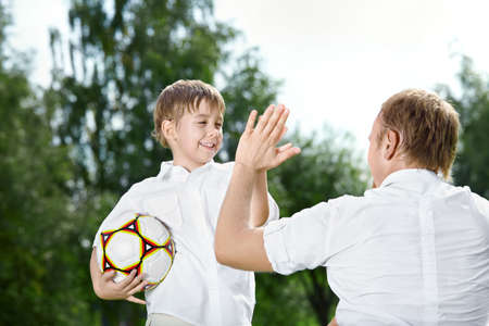 Small son - the football player welcomes the father, summer photo
