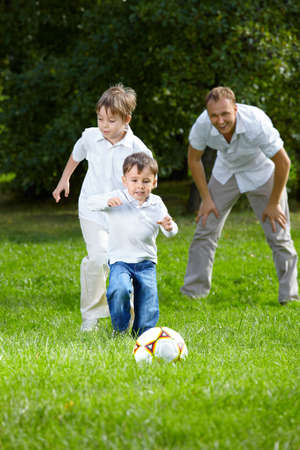 Competition of two little brothers in football in a summer garden photo