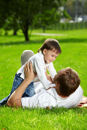 Cheerful father and son lie on a lawn in a summer garden