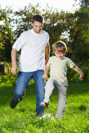 Cheerful father and son catch up with a football in park photo