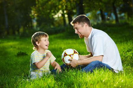 day of father: Padre e parlare con il figlio, seduto in parco con un pallone da calcio