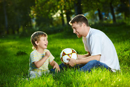 ni�os hablando: Padre, hijo y hablar, sentado en el parque con una pelota de f�tbol Foto de archivo