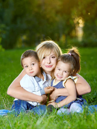 Mother embraces two children on a summer lawn Stock Photo - 5556716