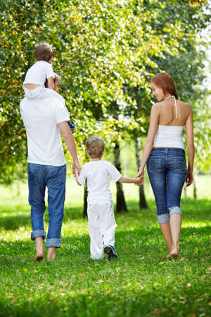 mom son: Rear view - a family with two children walks in park
