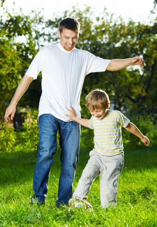 Father and small son play a ball in park Stock Photo - 5593950