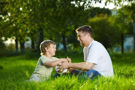 Conversaci�n de padre e hijo peque�o en un jard�n de verano Foto de archivo - 5593962