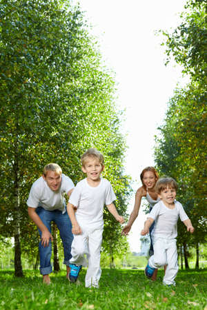 Cheerful parents release children to run in park photo