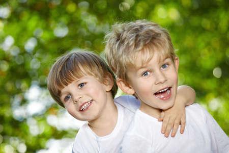 cute boys: Two cheerful boys embrace in a summer garden