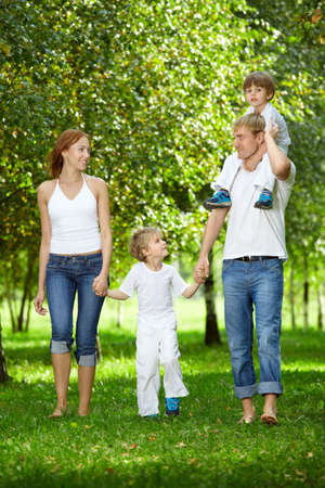 Happy family with two small sons goes on a summer garden photo