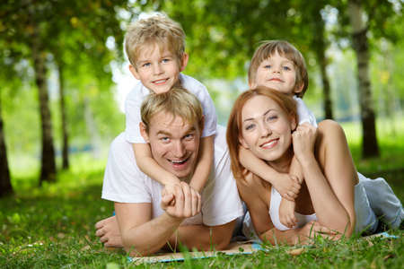 Happy family with two sons frolic on a lawn Stock Photo