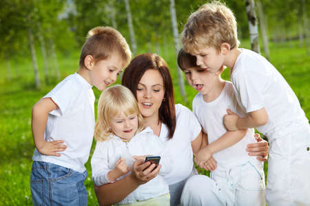 Four small child and mother are interested by a mobile phone in a summer garden photo