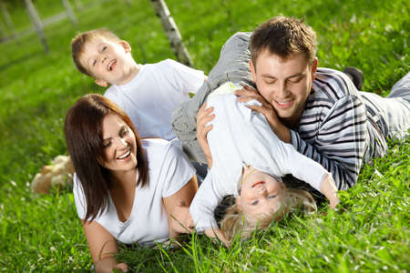 Young family with two small children frolics on a lawn photo