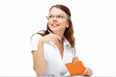 Ambitious business woman at table with a notebook and pen, isolated photo