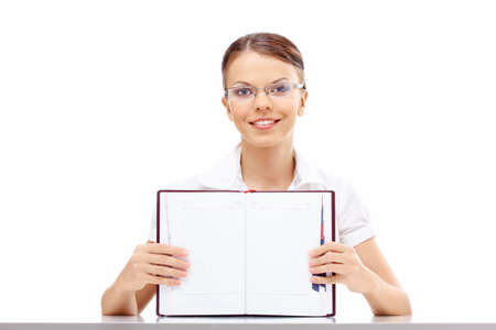 Attractive business girl shows the blank turn of a weekly journal, isolated photo