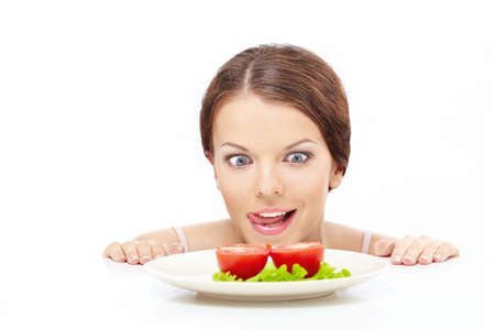licking finger: Hungry girl looks out from under table on plate with vegetables, isolated