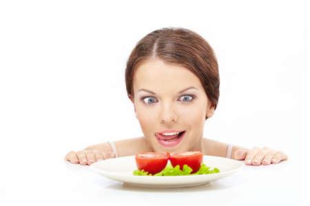 licking in isolated: Hungry ragazza guarda fuori da sotto il tavolo sulla piastra con verdure, isolata