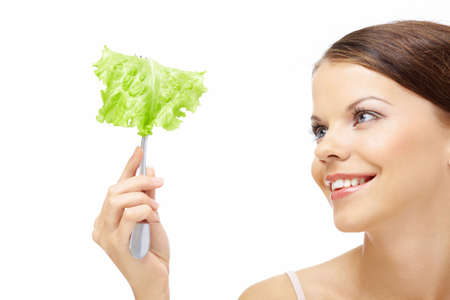Smiling girl looks at the leaf of salad isolated photo