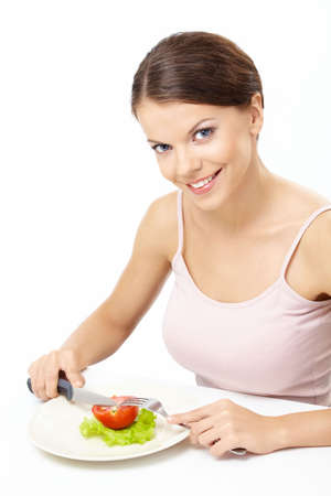 Smiling girl eats the vegetable salad, isolated photo