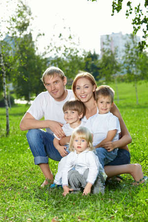Young family for five persons, has a rest in a summer garden photo
