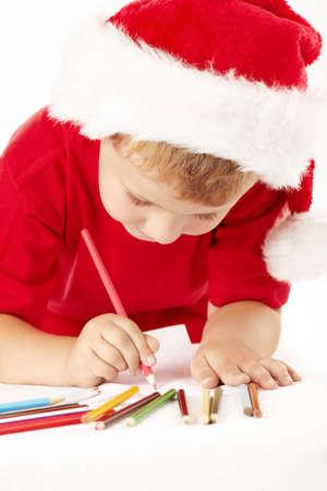 Little boy in a hat of santa draws on sheet photo
